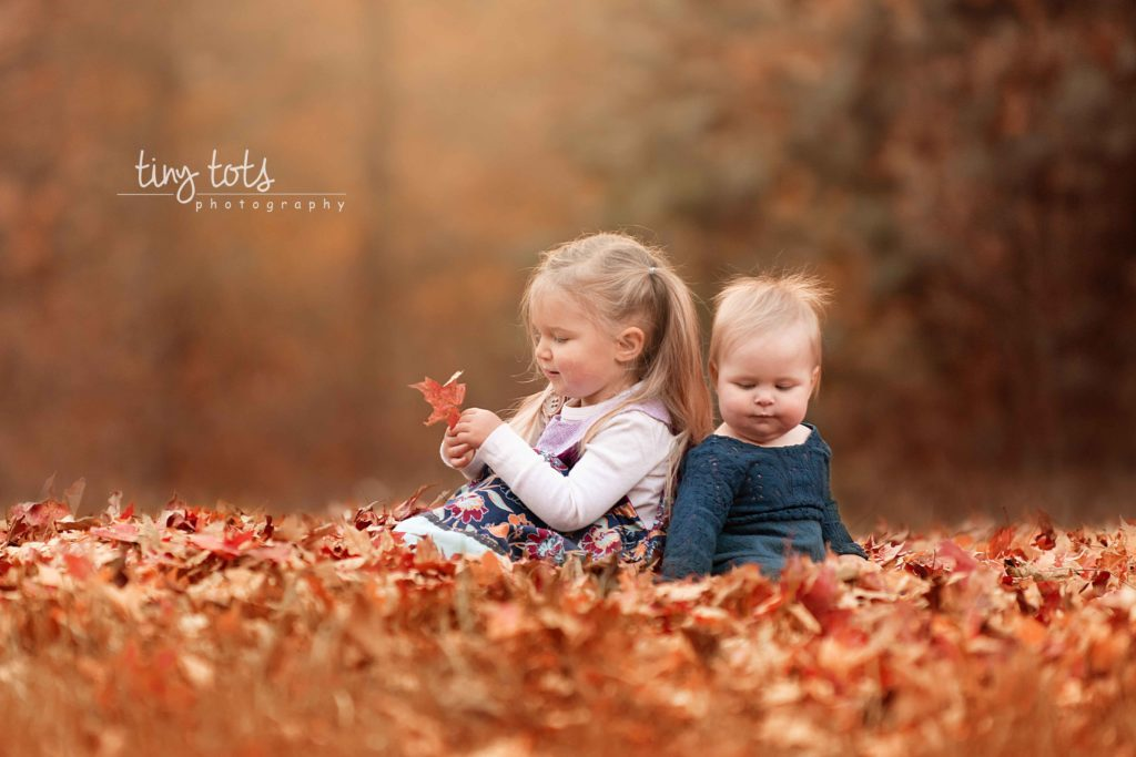 sisters-playing-fall-leaf-pile