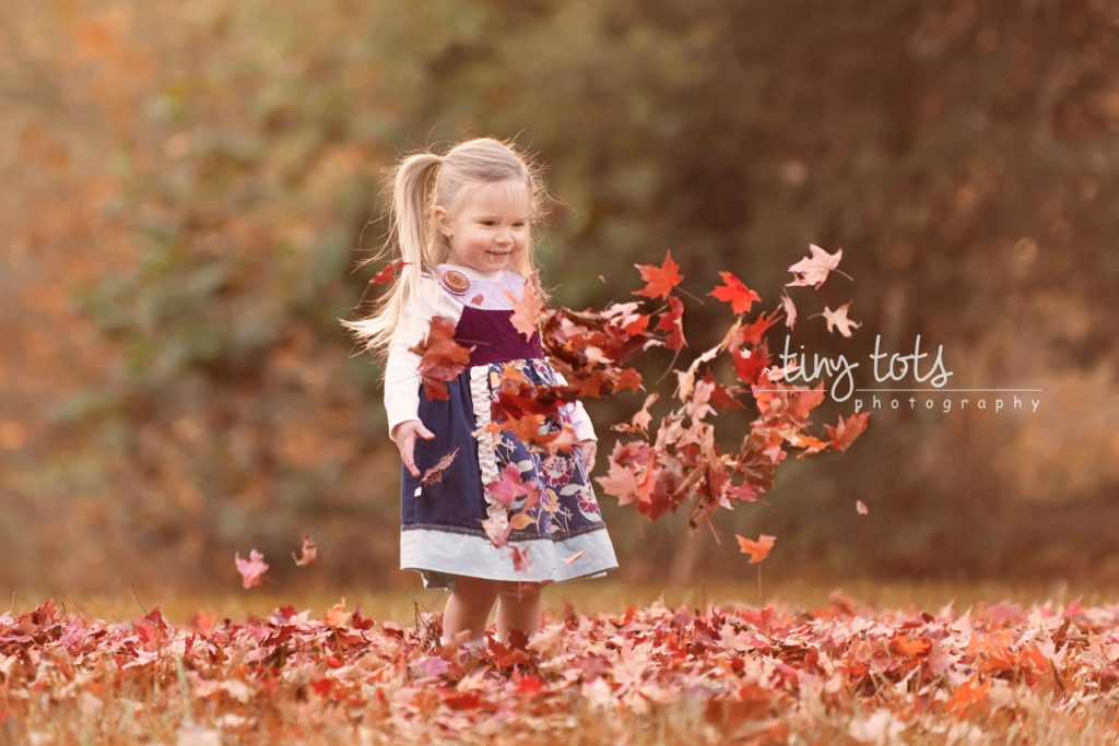 girl-throwing-fall-leaves