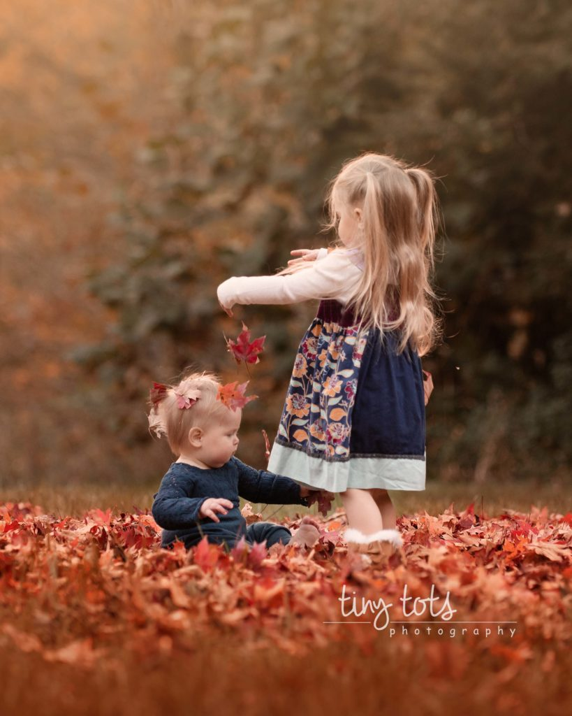 Sisters-playing-fall-colored-leaves