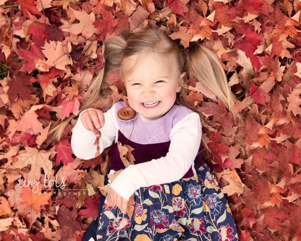 toddler-girl-laying-leaf-pile